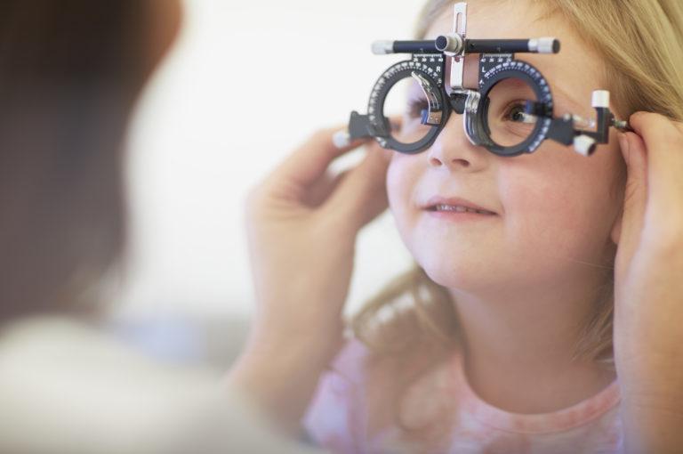 Eye doctor examining girl's vision