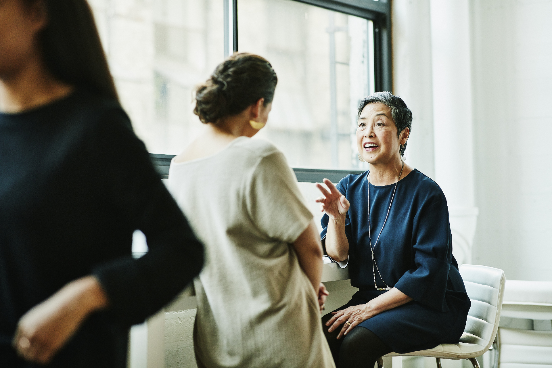 Smiling senior businesswoman leading project discussion with colleague in office conference room