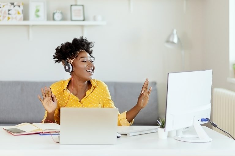Happy African American Businesswoman Having Fun While Working at Office Desk and Listening Music Over Headphones. Relaxed Young Woman in Headphones Enjoying Music Podcast Using Laptop App, Smiling Female Millennial Student or Office Worker Wearing Headset Listening to New Favorite Audio Tracks at Home or Work