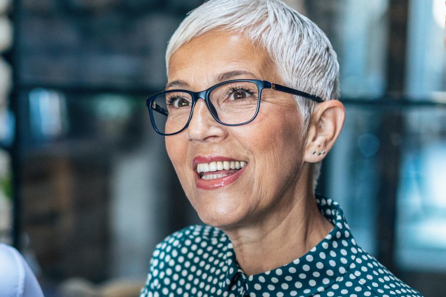 Une femme portant des lunettes bleues et souriant